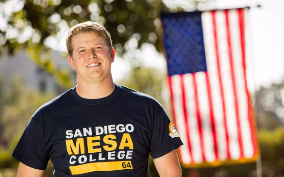 Calvin Dixon stands proudly, donning his San Diego Mesa College t-shirt in front of the American flag.